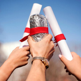 Raised hands clink diplomas and a Chipotle burrito in celebration of graduation