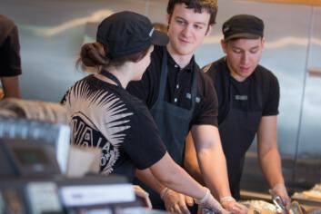 Chipotle Restaurant Manager está capacitando a un nuevo miembro de la tripulación para construir cuencos y burritos para los huéspedes del restaurante.