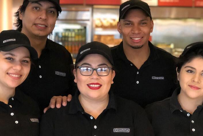Chipotle Restaurant Crew y Manager posan felices para una foto grupal en el restaurante.