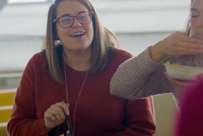 El personal de apoyo de Chipotle comparte una comida de Chipotle y se ríe en una conversación en el edificio de oficinas.
