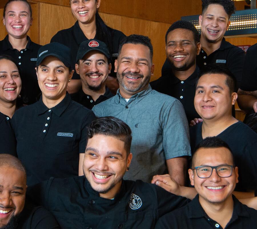 El líder de campo de Chipotle, Jhonson, comparte su historia de liderazgo y es retratado con un feliz grupo de miembros de la tripulación en un restaurante.