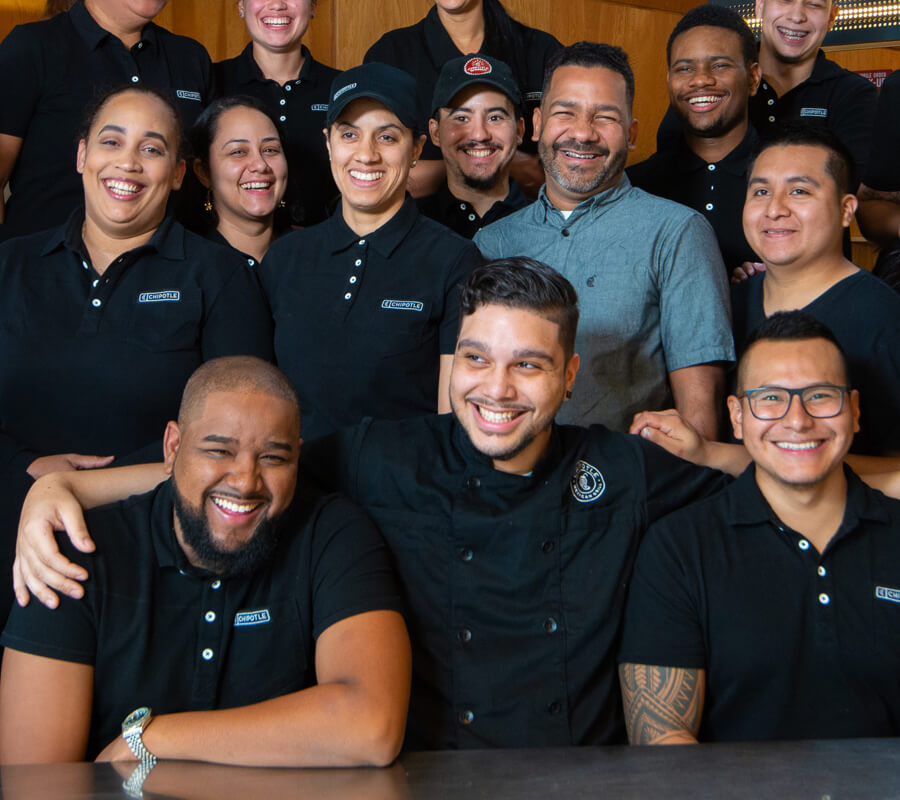 Los miembros de Chipotle Crew se reúnen en el restaurante para una feliz foto grupal.