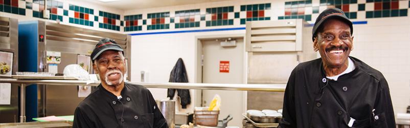 Two employees preparing food