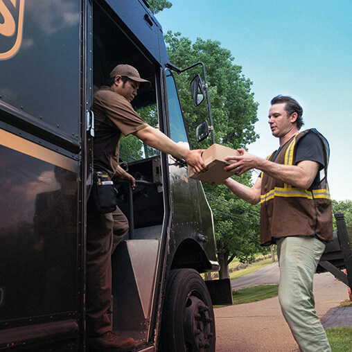 Employees delivering packages from a delivery truck.