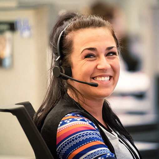 Employee smiling at the camera, while wearing a telephone headset.