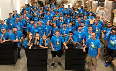Dozens of coworkers at a food bank volunteer event