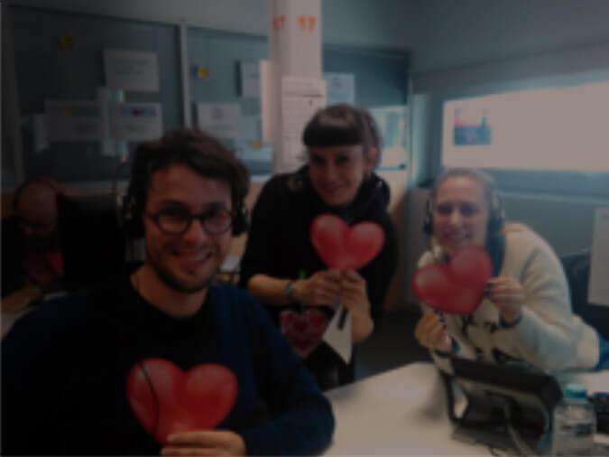 Três funcionários segurando corações