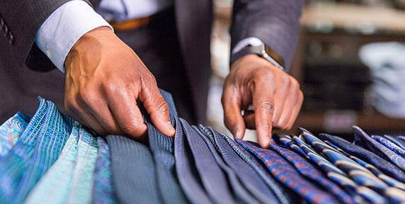man selecting necktie from table