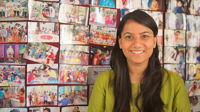 Image of Shrishti Warman standing in front of a wall of pictures
