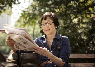 Woman with glasses reading newspaper on bench in park