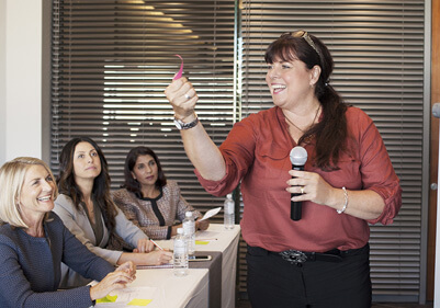 Woman with micrphone at front of classroom teaching