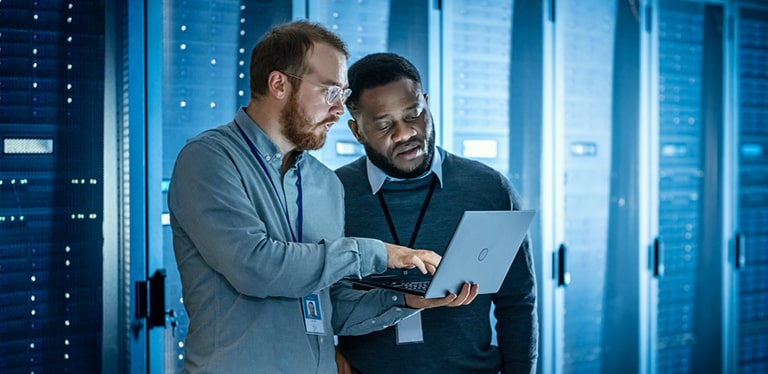 Two men in shirts and jumpers standing in a room full of server racks looking at a laptop screen