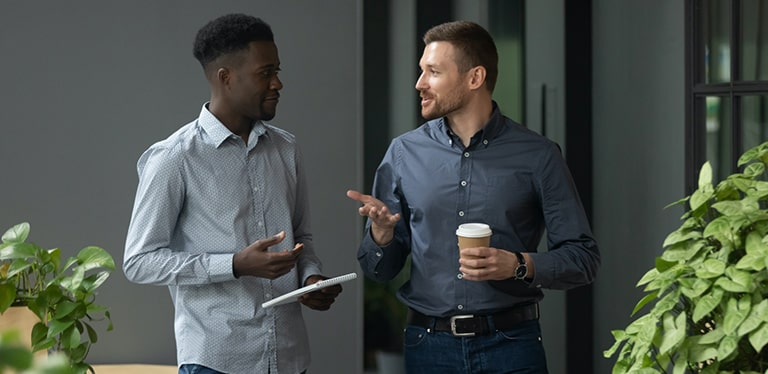Two men in shirts in a discussion. One is holding a notebook, the other is holding a coffee cup