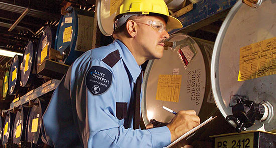 An employee looking at instrument readings on a wall of high-tech barrels.