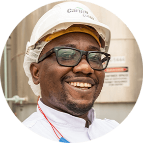 A black man wearing glasses and a white Cargill hardhat.