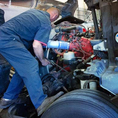Mechanics working on truck engine.