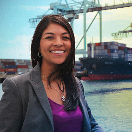 Employee outside smiling at a shipping terminal.