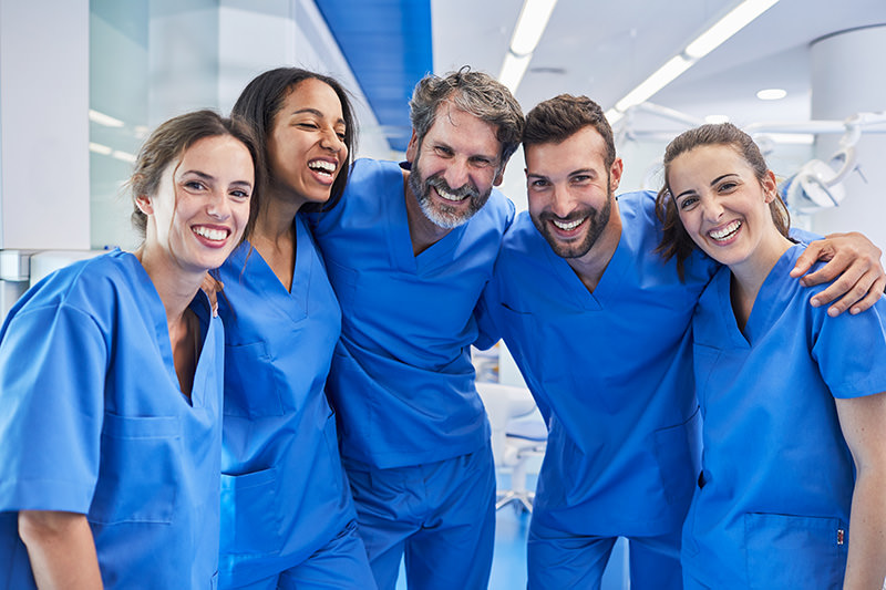 Team wearing blue scrubs smiling at the camera