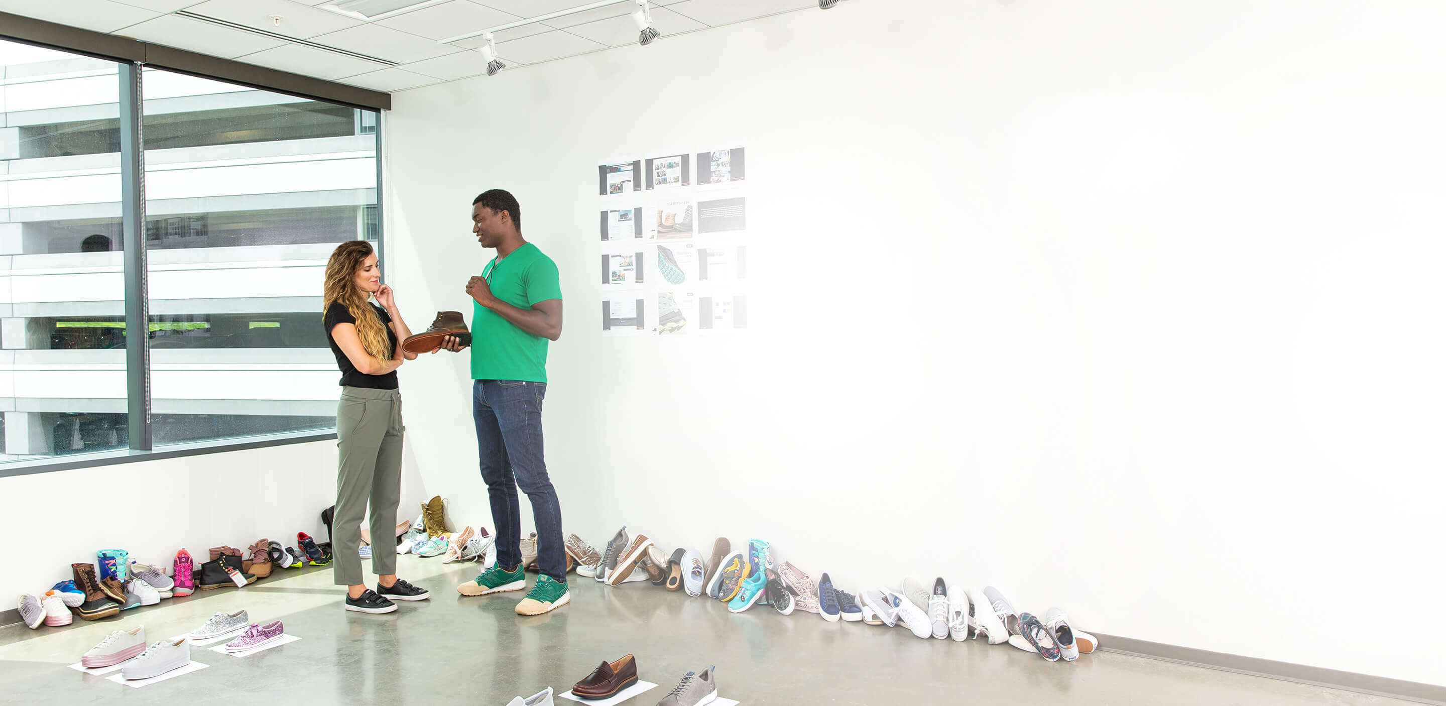 A man holds a boot while talking to a woman, shoes lined up along the walls