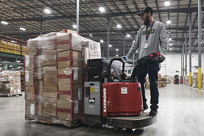 man driving forklift with packages