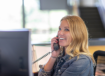 A woman smiles at her desk while talking on a landline phone