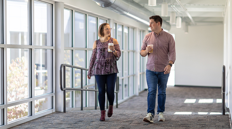 two people walking in a hall