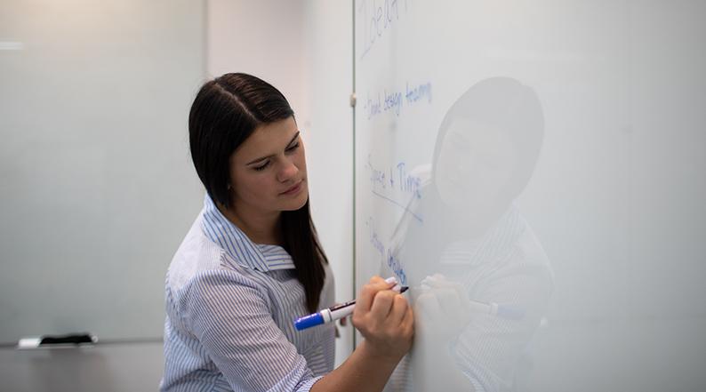 Woman writng on whiteboard
