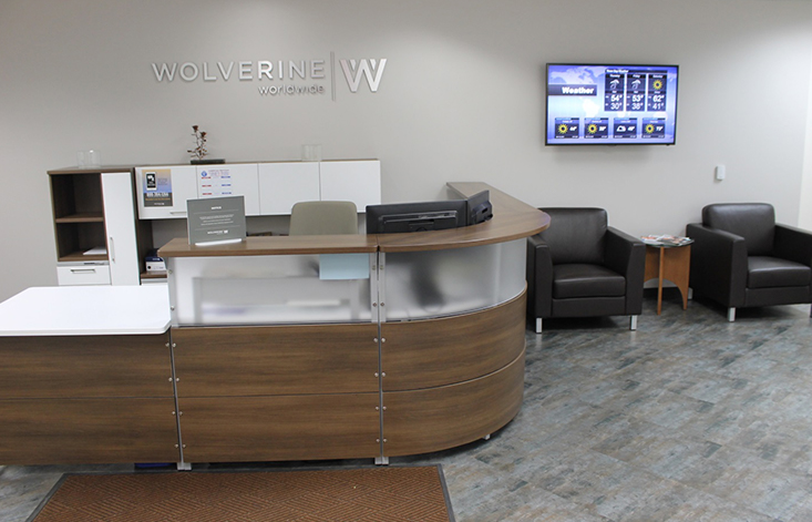 A receptionist's desk with the Wolverine logo on the wall