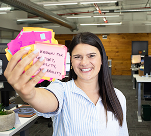 A woman smiles at the camera holding a stack of Post-it Notes