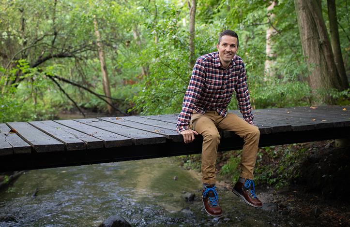 Jeff sitting on a bridge