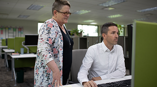 Jeff working on a computer with a woman observing