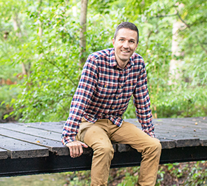A man sits on a bridge in a wooded area