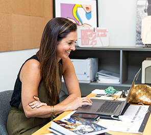 A woman smiles while working on her laptop