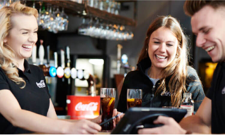 smiling staff in uniform working in a bar