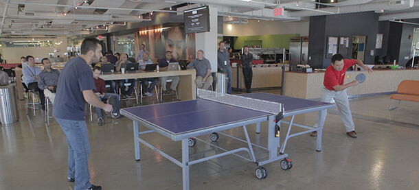 Employees playing ping pong.