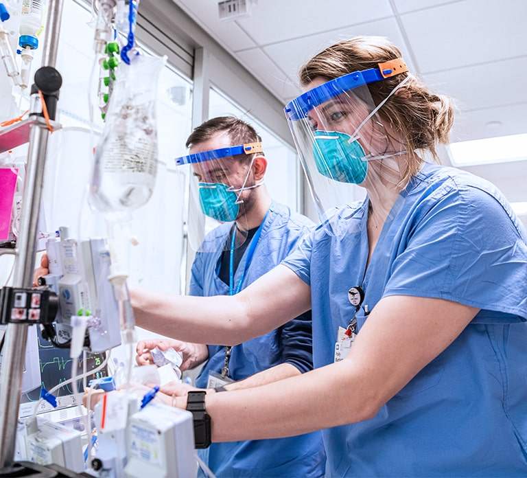 Male Nurse and Female Nurse working side by side and operating medical machinery