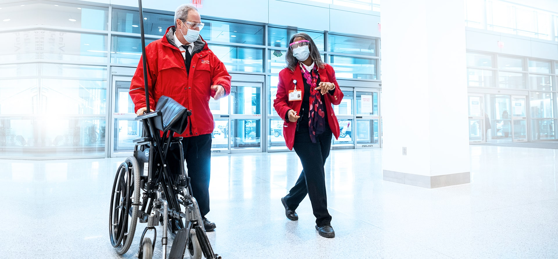 Male and female staff members wearing red jackets. The man is pushing an empty wheelchair
