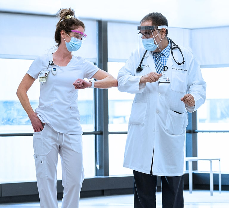 Female Nurse and Male Doctor wearing masks and visors touching elbows