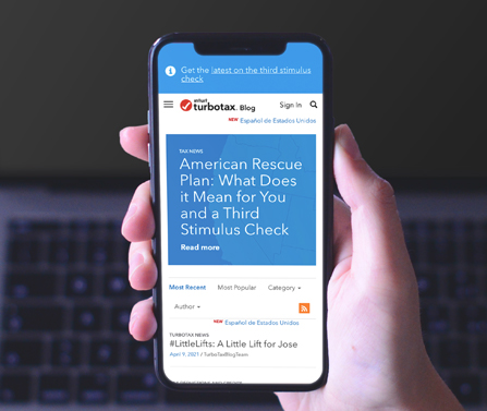 Person holding phone that has the TurboTax blog open