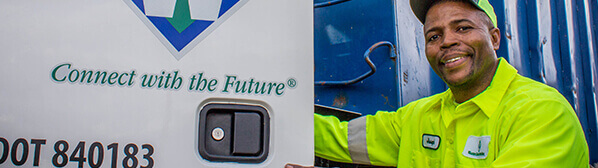 Smiling male employee, wearing yellow shirt and cap, opening a door with Waste Connections logo and tagline on it.