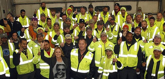 Group photo of Waste Connections employees with hands in the air