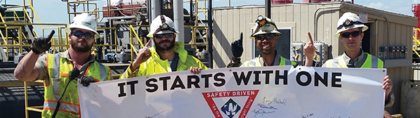 Four male employees wearing hard hats, sunglasses and yellow safety vests, holding a sign that says: 'It starts with one.'