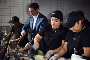 Chipotle Chairman and CEO, Brian Niccol, builds bowls and burritos with Chipotle Crew members in the restaurant.