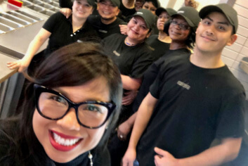 Chipotle Chief People Officer, Marissa Andrada, poses in a restaurant with happy crew members.