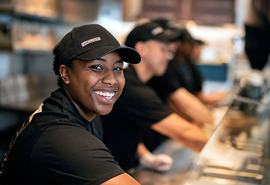 Chipotle Crew members work to happily serve bowls and burritos to guests in the restaurant