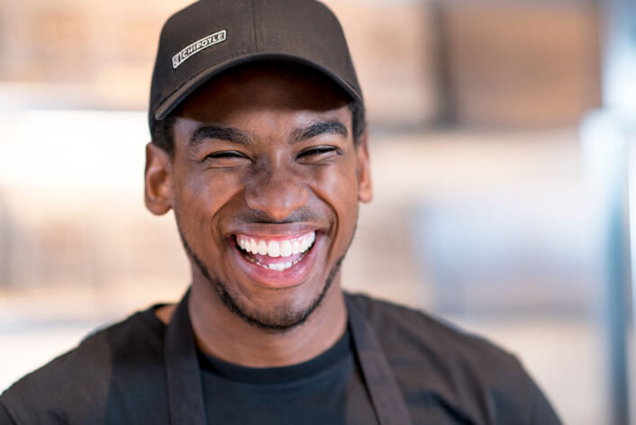 Chipotle Restaurant Crew team member laughs happily while serving guests in the restaurant.
