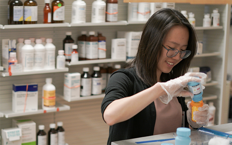 Woman filling a pill bottle in a pharmacy