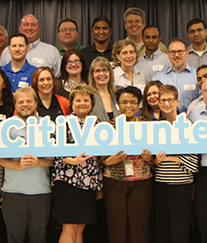 Citi employees on stage together during a volunteering event