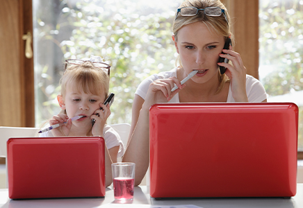 Mother and daughter each looking at laptops