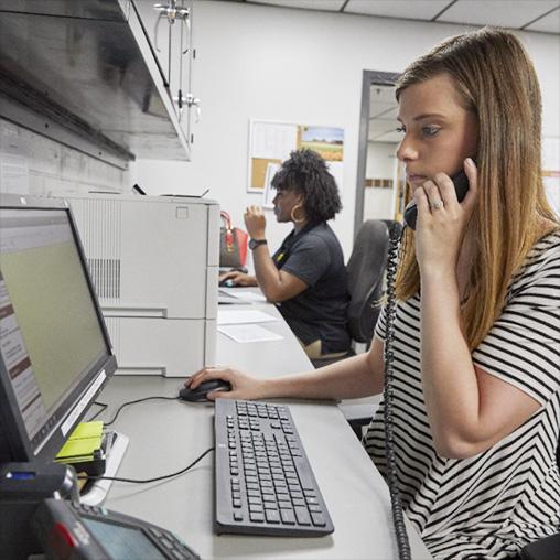 Woman at computer and answering phone